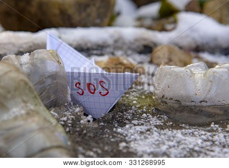 The Paper Boat Marked Sos Was Stuck Among The Plastic Bottles Frozen In The Water.