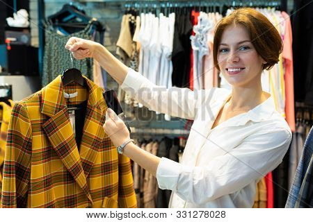 Attractive Caucasian Female Demonstrates Yellow And Brown Checked Jacket.