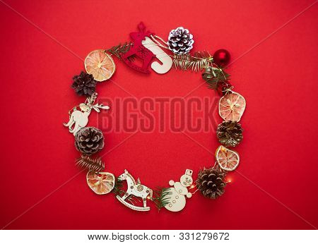 Chirstmas Wreath Decoration With Pine Cones, Balls And Toys. Flat Lay, Top View. Red Background. Cop