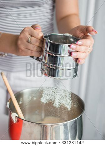 Hand Holds Metal Flour Sifter, A Sieve Sprinkled Flour. Sifting Flour. Preparation For Baking.