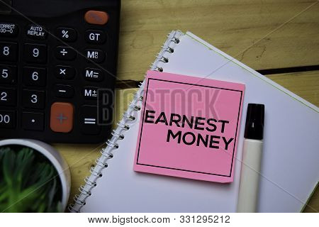 Earnest Money Write On Sticky Note With Wooden Table Background