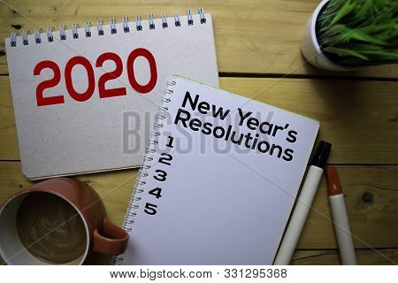 2020 New Year's Resolutions Write On The Book With Wooden Table Background