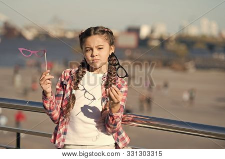 Which Props To Choose. Doubting Small Girl Choosing Glasses Props. Adorable Little Child Holding Pho