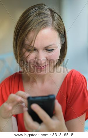 Young Adult Woman In Red Dress Sitting At Cafe Near Window, Looking Down And Internet Surfing In Sma