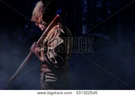 Photo Of A Scary Bloody Male Murderer In Brown Hood Jacket Holding An Axe In Dark Woods Background,