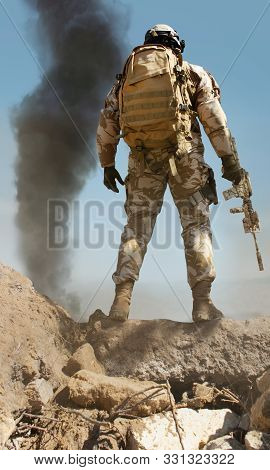 Photo Of A Fully Equipped Desert Soldier With Rifle Standing On Stone Mountain With Tactical Backpac