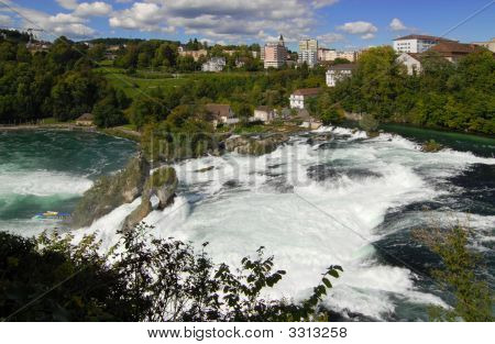 the rhine falls (in german language: rheinfall) the largest falls in europe offer a spectacular showpiece to visitors. with an average flow of 25'000 cubic ft / sec (700 m3 / sec) the water cascades down the cataracts which are 450 ft ( 150 m) wide and  poster