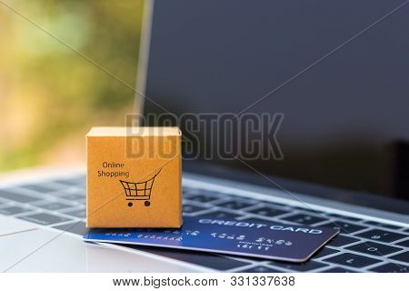 Online Shopping And Ecommerce Concept. Cardboard Box With Symbol And Mock-up Of Credit Card On Lapto