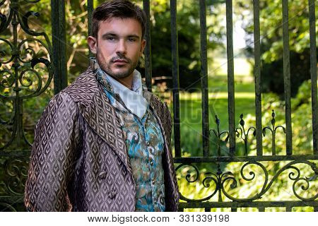 Portrait Of Handsome Gentleman Dressed In Vintage Costume Standing In Stately Home Courtyard With Ra