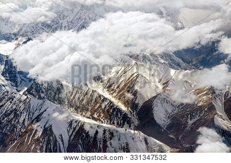 Sky Scenery.  Aerial View Above The Clouds At Mountain Peaks Covered With Snow,  Lighting By The Sun