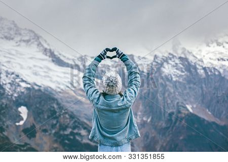 Back view of young traveler girl in gloves and hat standing over snowy mountain peaks and making shape of love heart by hands. Winter travelling scene, wanderlust concept.