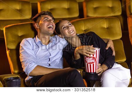 Young Man Laughing And Hugging Girlfriend With Popcorn Bucket While Watching Movie During Couple Dat