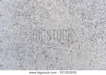 Gray Concrete Wall Interspersed With Small Stones Of Natural Rubble. Background
