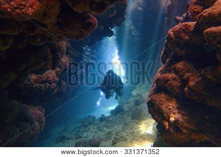 Scuba Diver Inside The Underwater Cave In Beautiful Natural Light