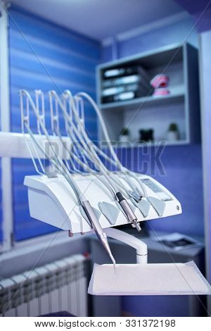 Modern metallic dentist tools and burnishers on a dentist chair poster