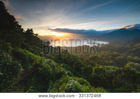 Beautiful Sunset over Lake Buyan Bali Indonesia. Island Coastal Scenery Nature Landscape. Amazing View on Green Bushes and Trees Forest Jungle Hill, Cloudy Sky and Sun. Shoreline from Climb