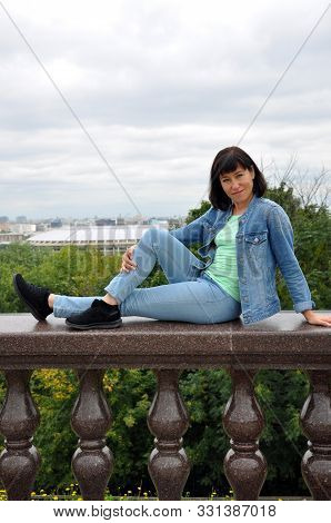 Beautiful European Young Woman Traveler Sits On The Parapet And Enjoys The Views Of Moscow. Vrorbiev