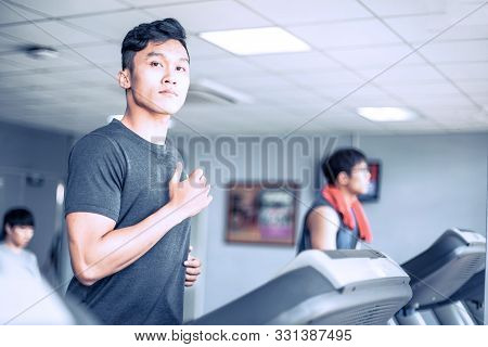 Handsome Young Atheletic Man In Sportswear Running On Treadmill At Gym