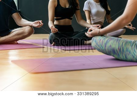 Cropped Shot Group Of Young Slim Body People Doing Yoga In Padmasana Or Lotus Yoga Pose On Yoga Mat