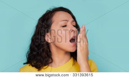 Health Care: Woman Checking Her Breath With Hand. Closeup Portrait Headshot Sleepy Young Woman With