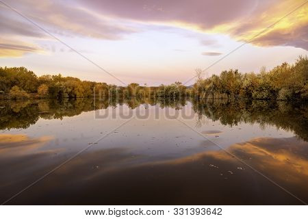 Fall Foliage Reflecting In The Lake At Sunrise