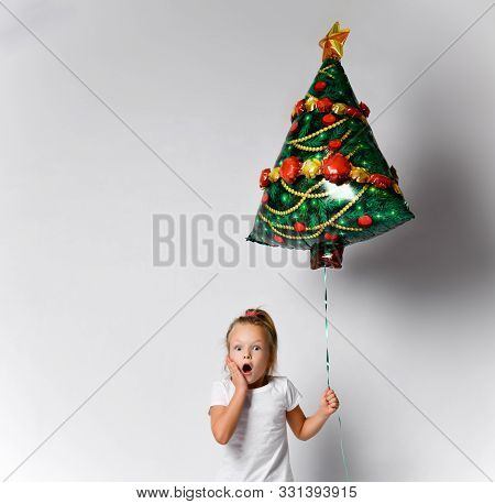 Little Kid Girl With Christmas Tree Air Balloon Is Awing, Surprised, Worrying On White Background Wi