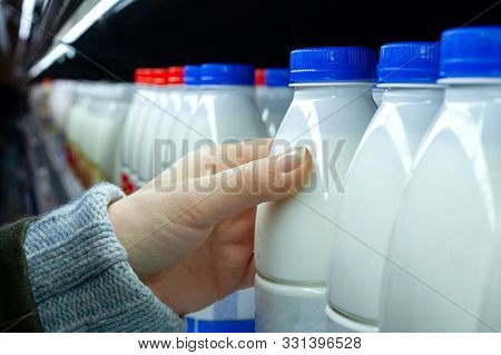 Womans Hand Holding Milk Bottle In Supermarket. Man Shopping Milk In Grocery Store. Close-up.