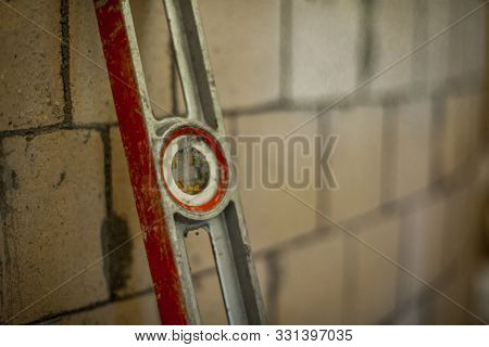 Close Up Of A Spirit Level Leaning On A Blurry Brick Wall