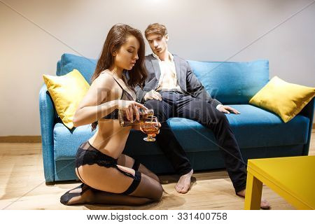 Young Sexy Couple Having Intimacy In Living Room. Man In Jacket Sit On Sofa And Look How Woman Pour