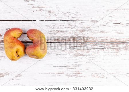 Ugly Fruits Pair Of Ripe Red Pears On White Wooden Table Background. Concept Of Zero Waste Productio