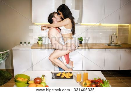 Young Sexy Couple Have Intimacy In Kitchen In Night. Woman Sit On Mans Hands And Embrace Him. Shirtl