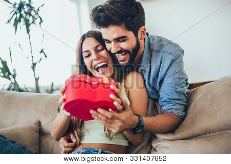 Happy Couple With Gift Box Hugging At Home. Handsome Man Is Giving His Girlfriend A Gift Box