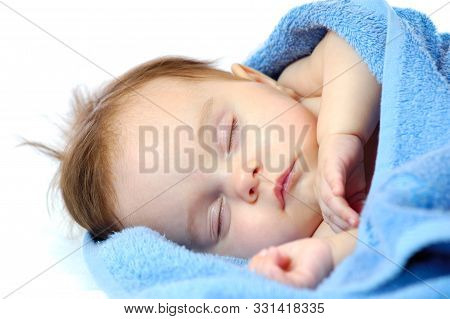 Close-up Portrait Of A Cute Little Girl Sleep In The Blue Towel On A White Background. Healthy Sleep