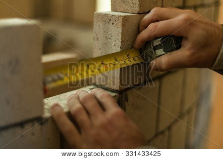 Brickmason Holding A Measuring Tape To Calculate The Distance Between Two Bricks While Constructing