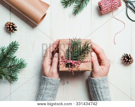 Christmas Gift Wrapping Background.female Hands Holding Christmas Present Box Wrapped In Kraft, Top