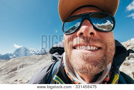 Ultra-wide Lens Angle Portrait Shot Of High Altitude Mountain Smiling Unshaven Happy Hiker In Baseba
