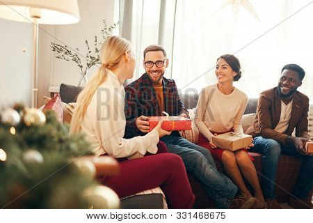 Group Of Elegant Adult People Exchanging Presents On Christmas, Focus On Bearded Man Smiling Happily