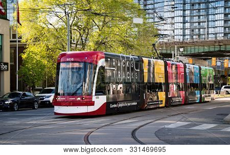Toronto, Canada - 06 09 2019: A New Bombardier-made Ttc Streetcar With Ad Banners On Its Sides Movin