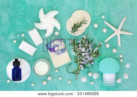 Skin care beauty treatment with fresh rosemary herb and cosmetic beauty products. Has astringent & anti ageing benefits & helps to reduce environmental skin damage. Flat lay on turquoise.