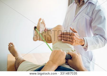 Confident Physical Therapist Helps Patient Use Resistance Band Stretching Out His Leg In Clinic Room