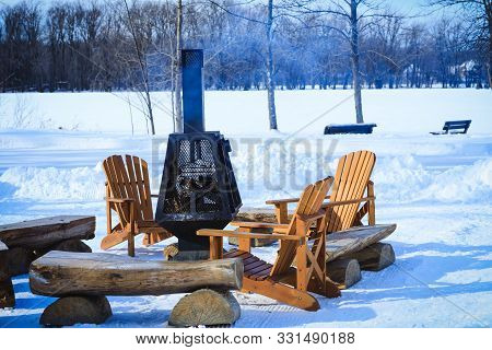 Wooden Benches And Chairs With Fireplace Charged With Firewood, In The Resting Place During Winter S