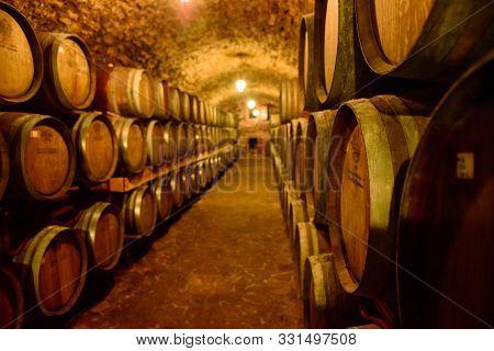 Wine Barrels In Wine-vaults In Order. Wine Bottle And Barrels In Winery Cellar