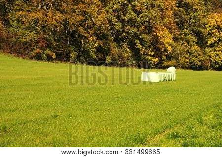 Silage Bales On Harvested Meadow In Hilly Rural Landscape In Autumn