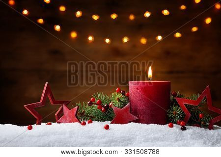 Christmas Or Advent Candle, Fir Branches, Berry And Red Stars In Snow Against Light  Garland Backgro