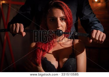 A Man Dominates And Puts A Gag In His Partner Mouth. Bdsm Concept. Portrait Of A Woman In Seductive