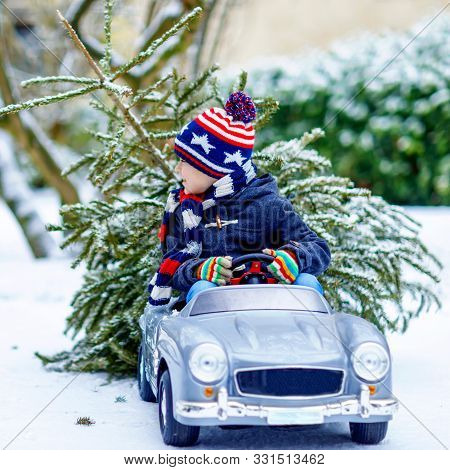 Lovely Little Smiling Kid Boy Driving Toy Car With Christmas Tree. Happy Child In Winter Fashion Clo