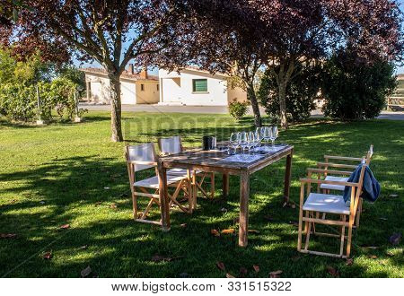 Table And Chairs Set Up Under The Trees And Prepared For The Wine Tasting  In A Small Local Winery N