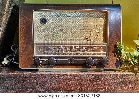 Old vintage radio set on a wooden shelf