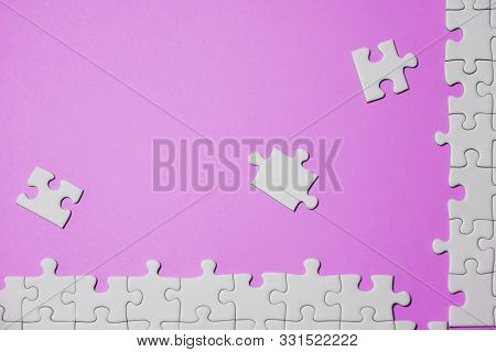 Missing Jigsaw Puzzle Pieces. Business Concept. Fragment Of A Folded White Jigsaw Puzzle And A Pile