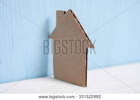Cardboard Cutout House Leaned Against The Wall On Blue Background. The Concept Of A Major Overhaul,